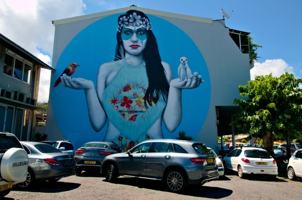 Mural showing Tahitian girl holding birds in her hands